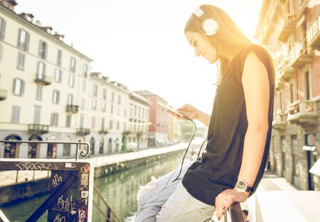 headset woman: woman listening to music with headset and smartphone in Milan. concept about technology and youth