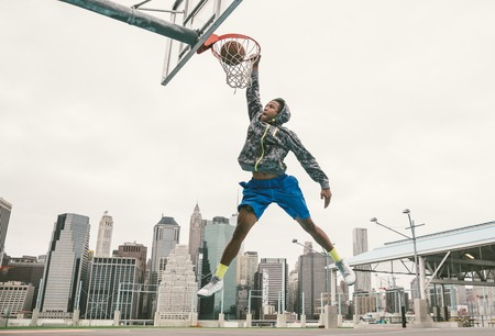 basketball game: basketball player performing slum dunk on a street court. background with manhattan buildings
