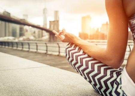 mujer que hace la posición de yoga en Nueva York City en la puesta del sol. Puente de Brooklyn y horizonte de Nueva York en el fondo Foto de archivo