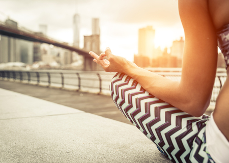 calmness: woman making yoga position in New york city at sunset time. Brooklyn bridge and new york skyline in the background