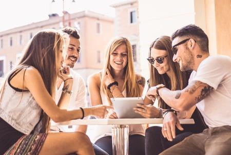 Groep vrienden kijken naar tablet in een bar