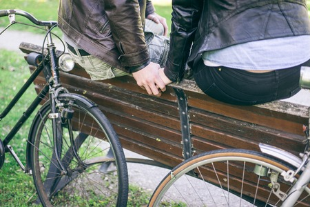 Couple holding hands after a bicycle ride. Couple relaxing on a bench in the park photo