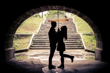 baiser amoureux: Couple d'amoureux étreignant sous un pont sur un jour de pluie - Silhouettes de l'homme et la femme sur une date romantique sous la pluie, en riant et amusent