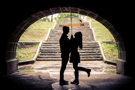 lovers embracing: Couple of lovers hugging under a bridge on a rainy day - Silhouettes of man and woman on a romantic date under the rain, laughing and having fun
