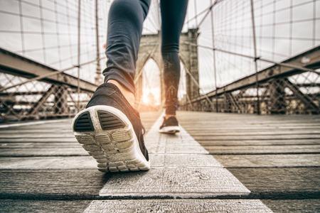 zapato: Mujer que se ejecuta al aire libre - muchacha juguetona joven que activa al atardecer en el puente de Brooklyn, de cerca en los zapatos Foto de archivo