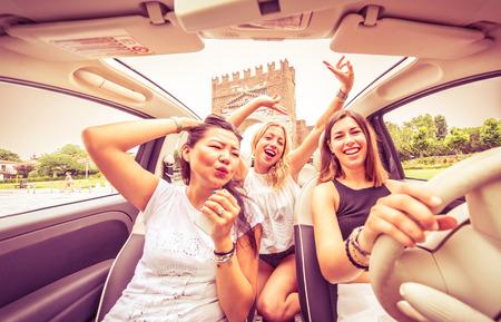 Gruppo di amici che hanno divertimento sulla vettura. Cantare e ridere nel centro della città