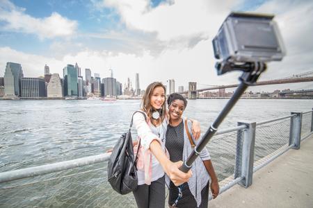 accion: Dos amigos femeninos que toman una foto de Nueva York y el puente de Brooklyn - Los mejores amigos viajando y grabando su viaje con una cámara de acción Foto de archivo