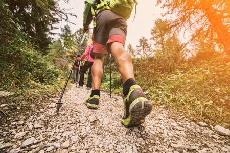 with friends: Grupo de excursionistas caminando en la naturaleza en la puesta del sol - Amigos que toman un excursionon una monta�a, Colse en el zapato