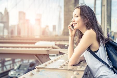 personas hablando: Mujer joven bonita que habla en el teléfono celular en el puente de Brooklyn - mujer de raza mixta que tiene una conversación en smartphone, ciudad al atardecer en el fondo