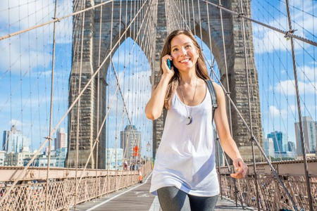 travel woman: Young pretty woman talking at cellular phone on Brooklyn Bridge - Mixed race woman having a conversation at smartphone