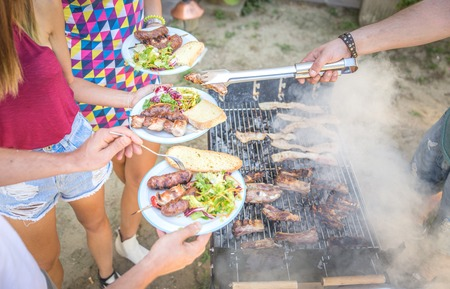 private party: Barbecue in home garden, Host serving his guests - Group of friends making barbecue and having fun at private party Stock Photo