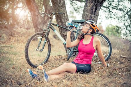 Atletische vrouw rusten en drinkwater na een ritje op haar mountainbike - Mooie jonge vrouw training met haar off-road fiets