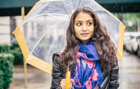 Mixed race woman walking on New York streets and holding umbrella on a rainy day - Portrait of asian woman in autumn