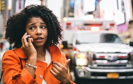 Afro-Amerikaanse vrouw belt 911 in New York City. Concept over auto-ongelukken en noodsituaties Stockfoto