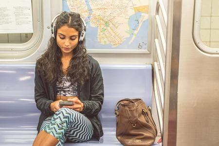 젊은 아시아 여자 지하철 차에 앉아 그녀의 스마트 폰으로 음악을 듣고 - 기차를 타고 예쁜 여자와 작업 할 것