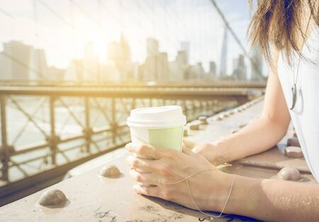 morning breakfast: Close up on a woman holding coffee paper cup on Brooklyn bridge in New york Stock Photo