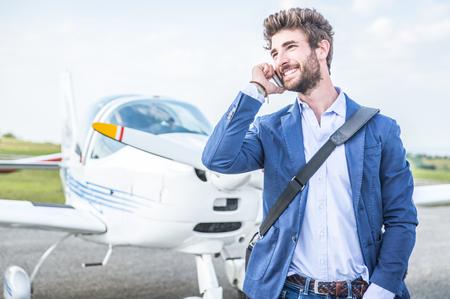 ビジネスの男性と彼の飛行機。彼はスマート フォンが付いている空港を歩いては、呼び出しを行います。 写真素材