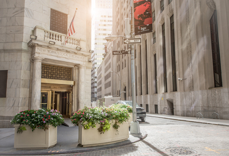 new york stock exchange: NEW YORK CITY, NY - OCTOBER 4, 2015: The side entrance of New York Stock Exchange and a street sign of Wall Street  in New York City. The Exchange building was built in 1903.