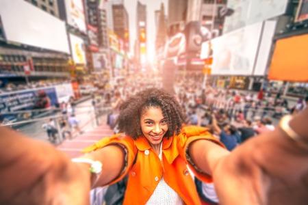 Красивая женщина, принимая selfie на Таймс-сквер в Нью-Йорке - Afroamerican девушка, принимая памятные автопортрет с смартфона во время поездки в переполненном городе Фото со стока
