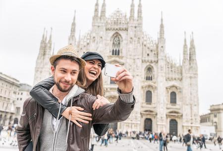 旅行: 快樂的遊客以自畫像與手機在Duomo大教堂,米蘭面前 - 在意大利旅行的夫婦 版權商用圖片