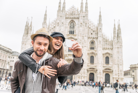 are taking: Happy tourists taking a self portrait with phone in front of Duomo cathedral,Milan - Couple travelling in Italy