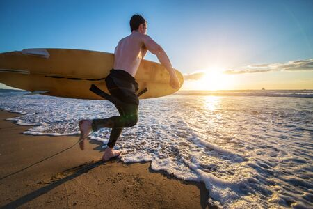 Surfer with board running into the the ocean at sunset - Sportive man going to surf on a tropical beach