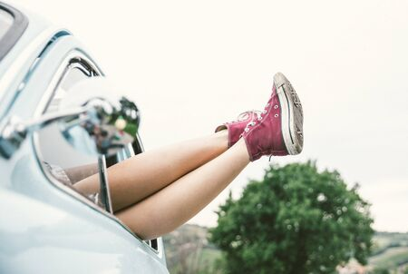young girl nude: Woman legs outside a vintage car. concept about carefree and freedom Stock Photo