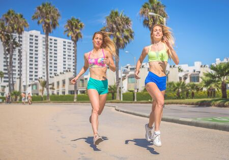 sportive: Two beautiful young girls running on a path outdoors . Sportive girl training on the beach on a beautiful warm sunny day Stock Photo