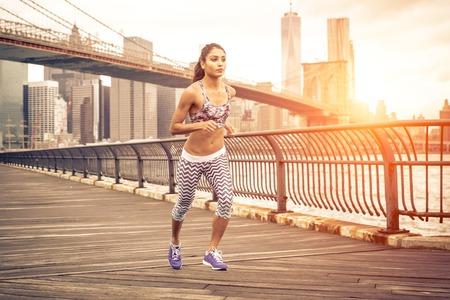 corriendo: hermosa mujer asiática que se ejecuta en Nueva York en la puesta del sol. Puente de Brooklyn y horizonte de Manhattan en el fondo