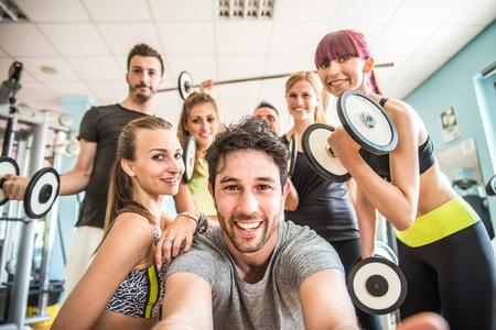 健身: 嬉戲的人在健身房採取selfie集團 - 在舉重室快樂運動的朋友,而培訓 - 關於生活方式和運動的健身俱樂部概念 版權商用圖片