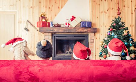 red couch: Three friends and a dog sitting on the couch in front of the fireplace. Concept about holidays and christmas
