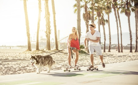 airiness: Couple having fun with their Husky dog. the animal pulling while the woman is on the skateboard