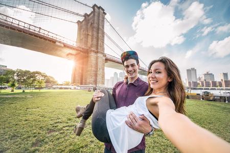 Молодые довольно пара, принимая селфи на Бруклинский мост, Нью-Йорк - Boyfriend держа свою подругу и веселятся при обзорная