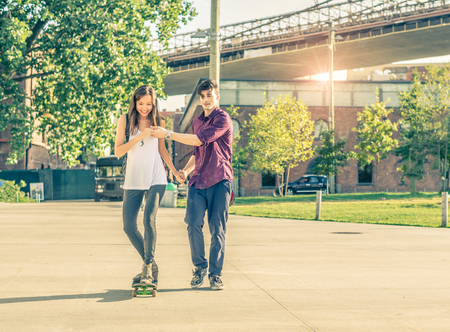 teaching: Young playful couple having a romantic date outdoors - Sportive man teaching her girlfriend to skateboarding - Teen lovers spending time together and having fun