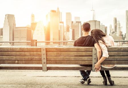 カップルは、日没時にスカイラインの前にニューヨークのベンチでリラックス。愛、関係、および旅行についての概念