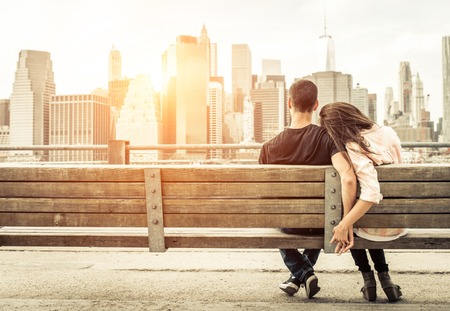 new york skyline: couple relaxing on New york bench in front of the skyline at sunset time. concept about love,relationship, and travel