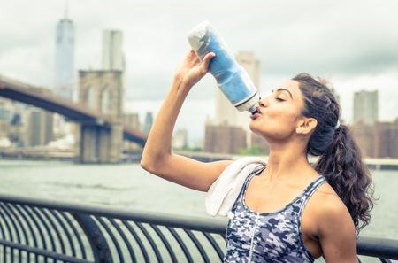 or thirsty: Sed para beber atleta despu�s de largo plazo en Nueva York. Puente de Brooklyn y horizonte en el fondo Foto de archivo