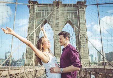 parejas romanticas: feliz pareja abraz�ndose unos a otros en el famoso puente de Brooklyn. concepto de amor, los viajes y la gente