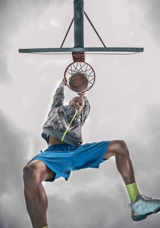 nba: Sportive man hanging from the basket and looking down triumphant at camera after a slam dunk - Basketball player sroring for his team