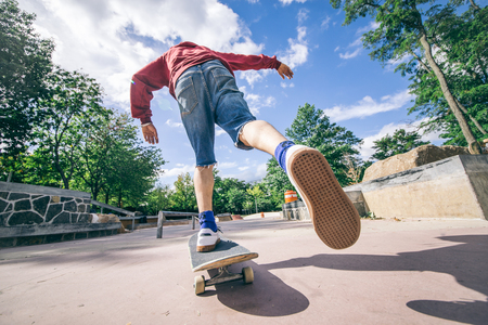 skateboard shoes: Skateboarder driving his board in a skate park - Young man attempting a trick with his skate
