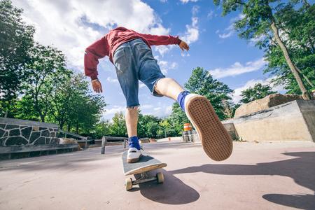 Skateboarder rijden zijn bord in een skatepark - Jonge man probeert een truc met zijn schaats