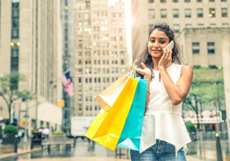 compras compulsivas: Mujer atractiva joven que recorre en las calles con bolsas de compras - compras de la chica asiática, mientras que llamando a su teléfono celular friendwith Foto de archivo