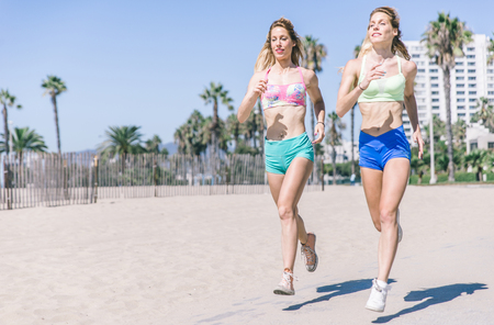 twins: Twin sisters running in the morning in Los angeles beach on the walkway Stock Photo