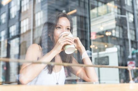 windows: hermosa chica disfrutando de un café caliente en el interior de una tienda en Nueva York Foto de archivo