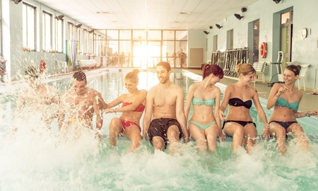 Group of friends having fun in the swimming pool. Splashing water around and laughing together Stock Photo