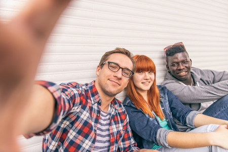 ethnics: Group of friends of different ethnics taking a selfie - Young modern hipster people having fun and laughing - Multiracial group photographing themselves and looking into camera