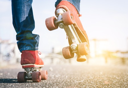 adult 80s: Skater close up in action. Roller skates shoes with sun beam in the background.