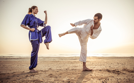 shu: Couple training martial arts techniques in the morning, on the beach Stock Photo