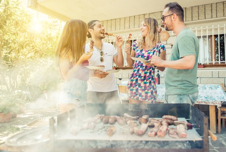 friends fun: Group of friend having lunch in the backyard. making barbecue outdoor with differnt kind of meat and vegetables Stock Photo