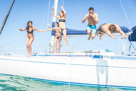 picada: Grupo de amigos saltando de la barca. que se divierte en el yate y en el agua